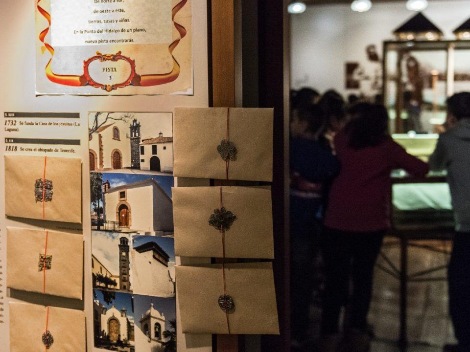 Instantánea tomada durante la realización del kit educativo. Muestra una serie de sobres colocados sobre uno de los paneles del museo y al fondo un grupo de niños.