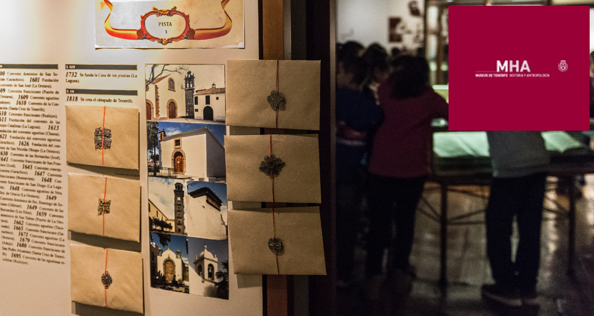 Instantánea tomada durante la realización del kit educativo. Muestra una serie de sobres colocados sobre uno de los paneles del museo y al fondo un grupo de niños. Con logo
